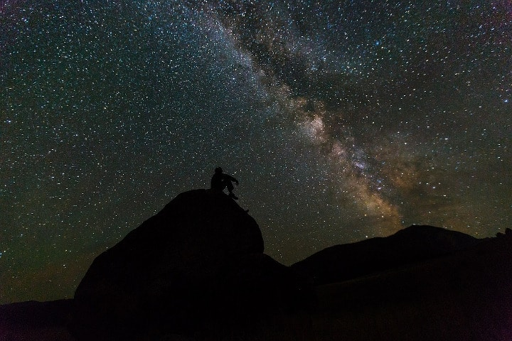man at night sitting under the stars and milky way