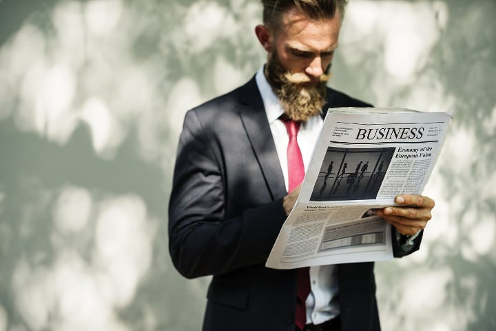 man in a suit with a beard reading a newspaper