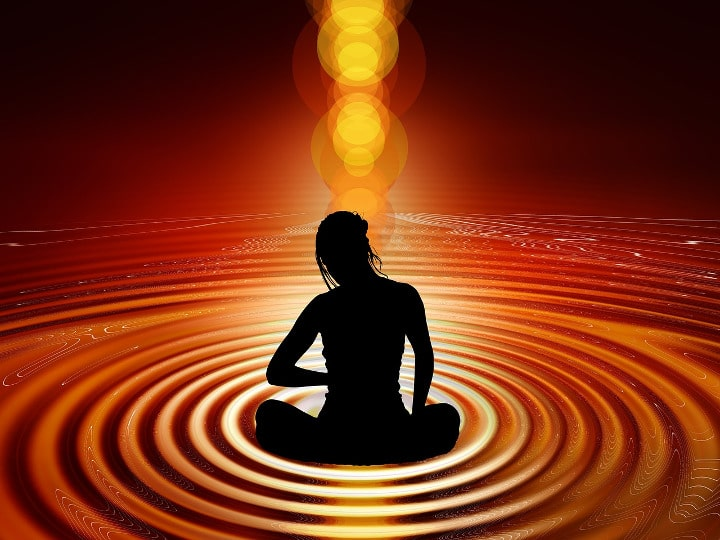 Black outline of a woman meditation in rippling pool of orange energy