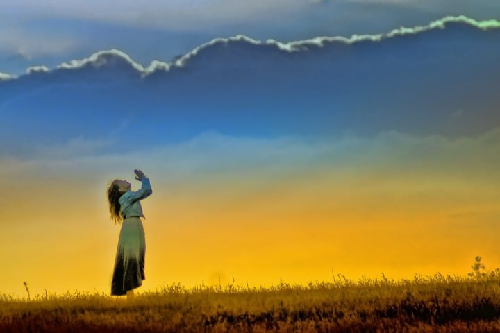 Woman in a field praying under the sunset