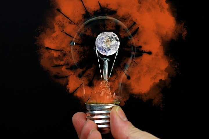 lightbulb in someones hand with orange smoke coming off with the earth in the center of the bulb