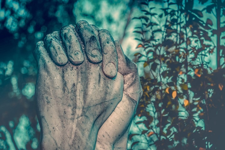 stone hands praying in forest