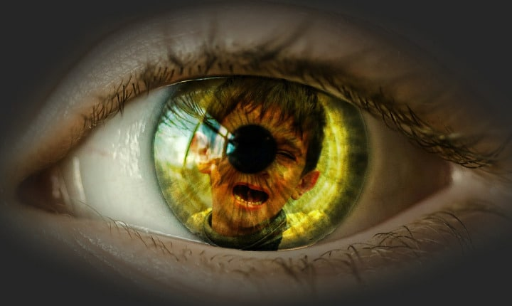 reflection of young boy suffering in an eye