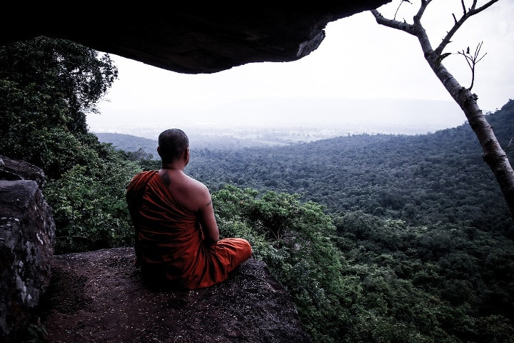 monk meditating outside of cave entrance overlooking a forest